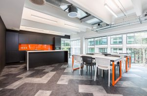 Company using orange and black its brand colours in breakout area.