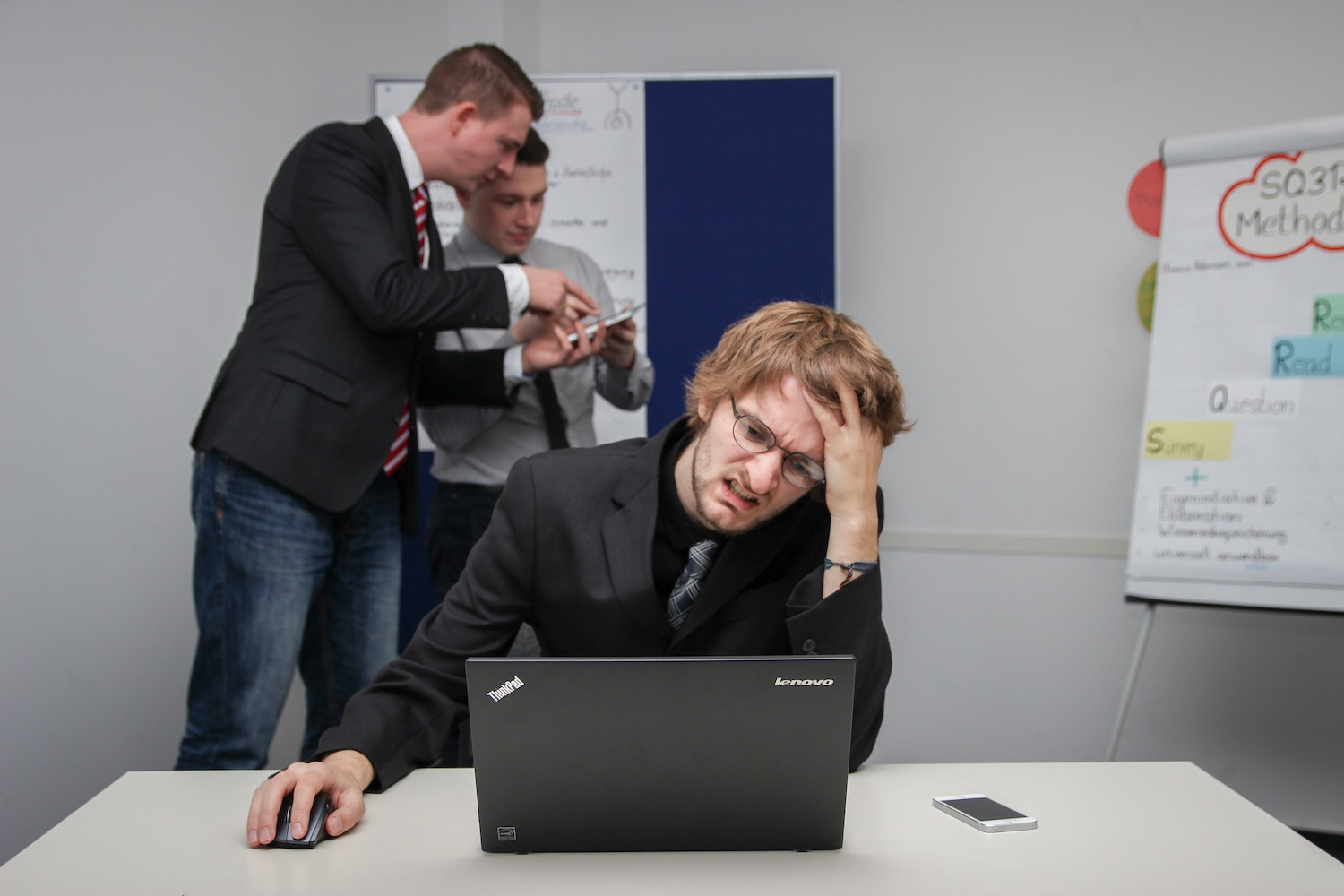Man hands on head looking stressed in office