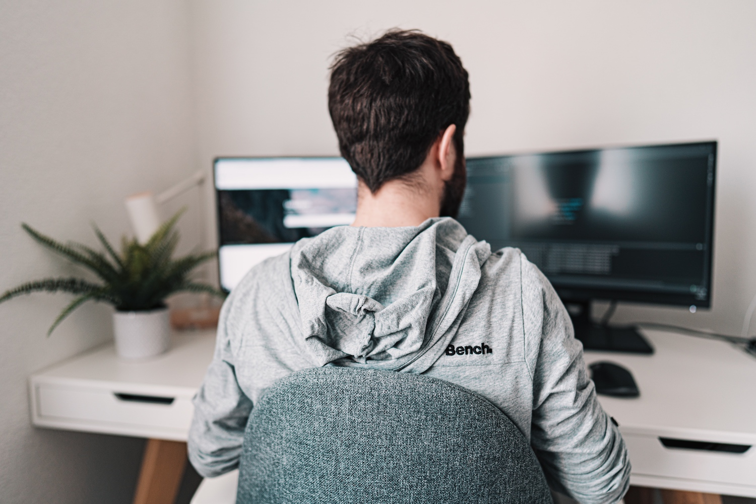 Man working remotely two computer screens